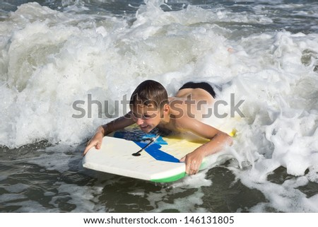 Bodyboarding. Child slides on a short board on a soft wave - stock photo