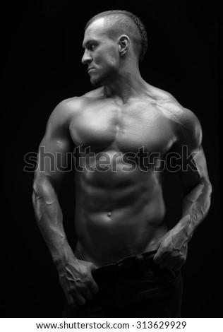 Bodybuilder and strip theme: beautiful with pumped muscles naked man posing in the studio on a dark background, black-and-white photo