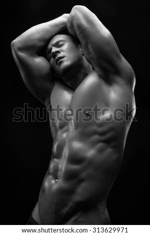 Bodybuilder and strip theme: beautiful with pumped muscles naked man posing in the studio on a dark background, black-and-white photo - stock photo