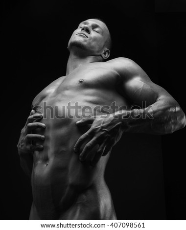 Bodybuilder and strip theme: beautiful with pumped muscles naked man posing in the studio on a dark background, black and white photo shot - stock photo