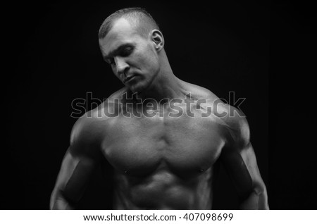 Bodybuilder and strip theme: beautiful with pumped muscles naked man posing in the studio on a dark background, black and white photo shot