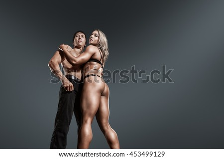 Bodybuilder athletic man and woman showing muscles in front of dark background - stock photo