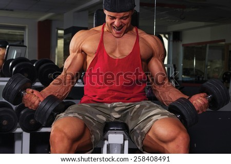 Bodybuilder biceps workout with dumbbells. - stock photo