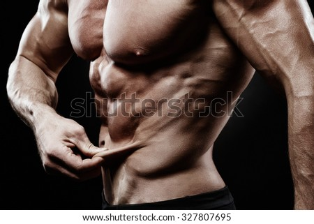 bodybuilder demonstrates a lack of fat on my stomach. muscular body on a black background - stock photo