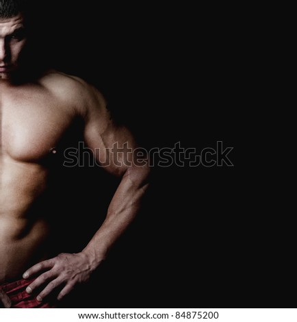 Bodybuilder demonstrates his muscular body. Isolated on black background. - stock photo