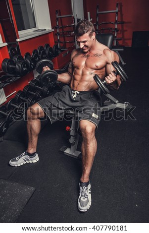 Bodybuilder doing biceps workouts in a gym club.