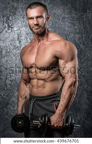 Bodybuilder doing exercises with dumbbells - stock photo