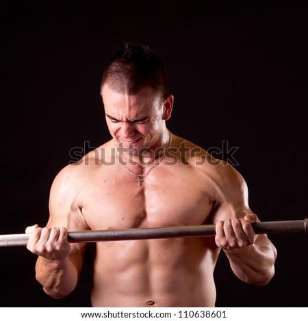 Bodybuilder exercising in front of black background - stock photo