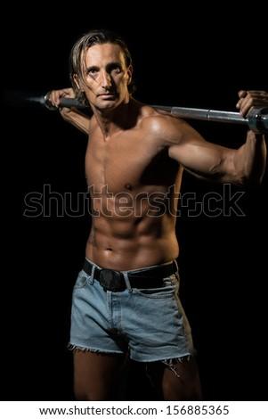 Bodybuilder Exercising Isolated On Black Background - stock photo