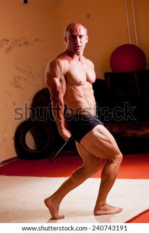 Bodybuilder fexing his muscles in a gym - stock photo