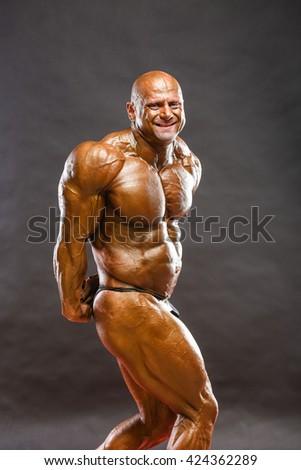 Bodybuilder flexing his muscles in studio - stock photo