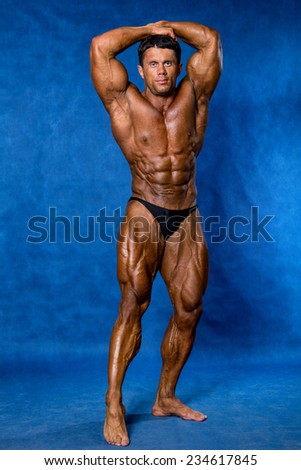 Bodybuilder flexing his muscles. Mandatory poses bodybuilders. On a blue background - stock photo