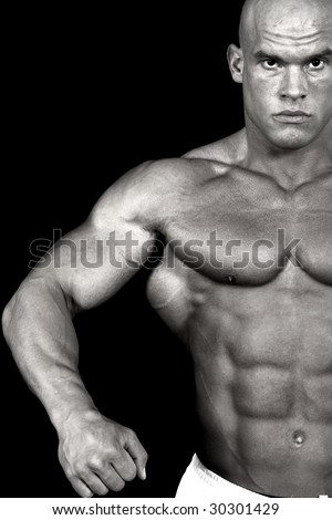 Bodybuilder flexing muscles to show off his strength-desaturated and isolated on black background