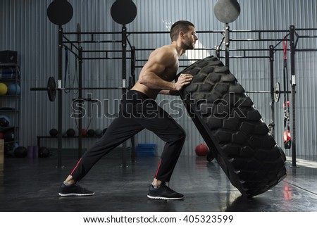 Bodybuilder flipping tire at the gym - stock photo