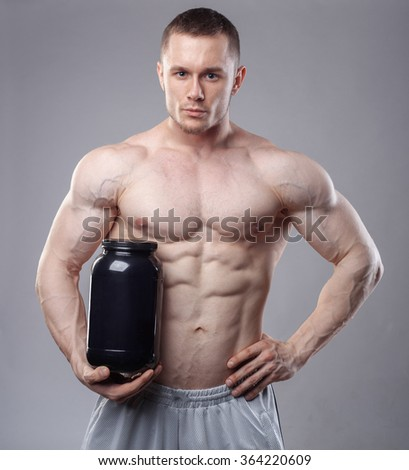 Bodybuilder holding a black plastic jar with whey protein on grey background. - stock photo