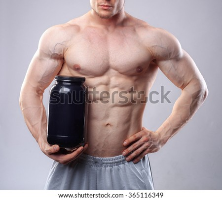 Bodybuilder holding a black plastic jar with whey protein on grey background. Without face - stock photo
