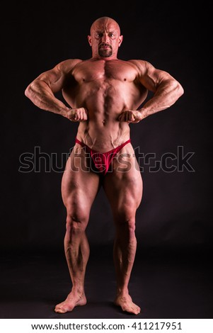 Bodybuilder in demonstrative poses on black - stock photo