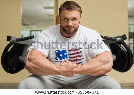 Bodybuilder in gym. Sportsman sitting at trainers. Mirror on the wall in gym. - stock photo