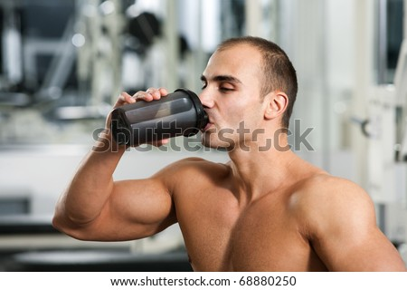 bodybuilder in the gym, drinking a protein shake - stock photo