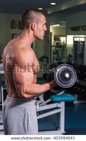 Bodybuilder in the gym. Strong performs exercises for biceps