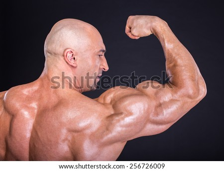 Bodybuilder is posing, showing his muscles. Force, relief, muscle, courage, virility, bodybuilder, bodybuilding. The concept of a healthy lifestyle. - stock photo