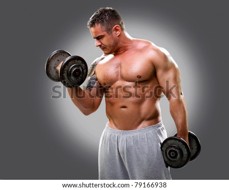 Bodybuilder lifting dumbbells and posing - stock photo