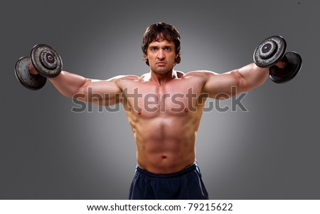 Bodybuilder lifting 12 kg dumbbells and posing - stock photo