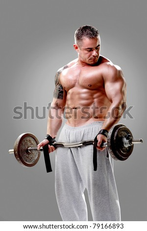 Bodybuilder lifting weights and posing - stock photo