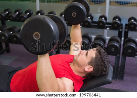 Bodybuilder lying on bench lifting dumbbells at the gym - stock photo