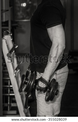 Bodybuilder makes exercise with dumbbells at the gym. Work on hands tell muscles. Exhausting workouts to an end. Photos for sporting magazines and websites.