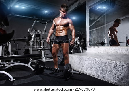 Bodybuilder man posing in the gym - stock photo