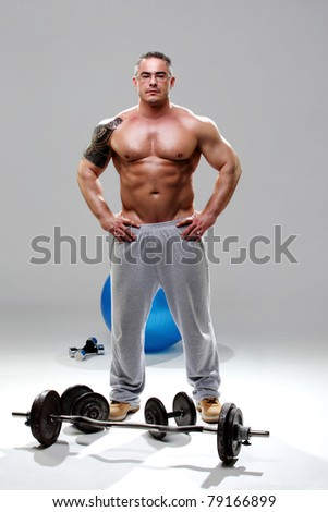 Bodybuilder naked on top, posing in front of the weights - stock photo