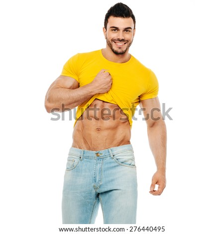 Bodybuilder or personal trainer pulling his t-shirt up and smiling at the camera on white background - stock photo