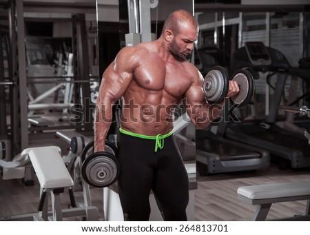 Bodybuilder performing dumbbell curls. - stock photo
