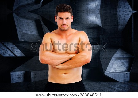 Bodybuilder posing against dark room