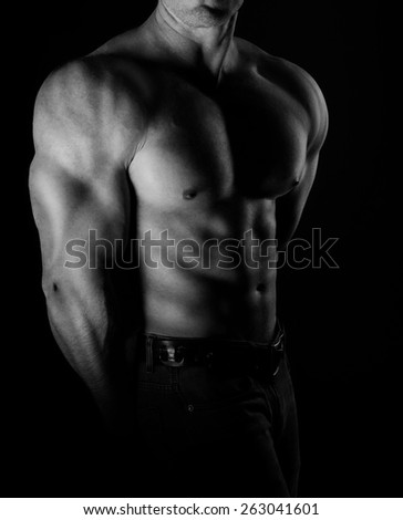 bodybuilder posing. Handsome power athletic guy male. Fitness muscular body on black background. Black and white photo - stock photo