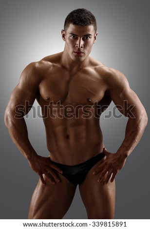 Bodybuilder posing. Handsome power athletic male. Fitness muscular body on gray background  - stock photo