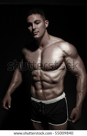 Bodybuilder posing in front of the camera. Black background and sharp light. Strengthened muscles with the help of the program. - stock photo