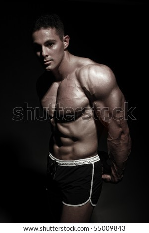 Bodybuilder posing in front of the camera. Black background and sharp light. Strengthened muscles with the help of the program.
