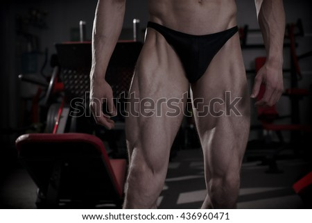 Bodybuilder posing in gym. Perfect muscular male legs. Toning image - stock photo