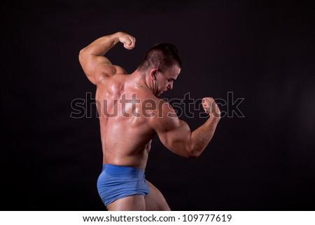 Bodybuilder posing in studio, flexing his lats - stock photo