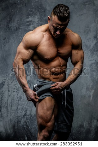 Bodybuilder posing in studio on grey background - stock photo