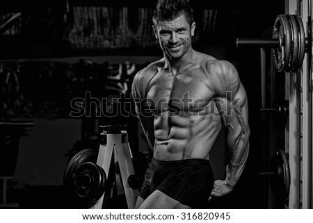 Bodybuilder posing in the gym - stock photo