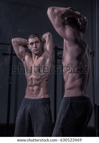 bodybuilder posing, looking at himself, double mirror image, musuclar shirtless body