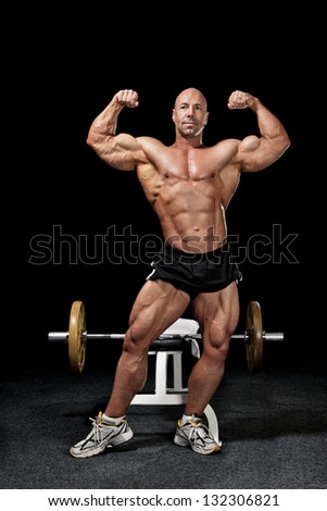 Bodybuilder posing near workout bench in gym with barbell isolated on black - stock photo