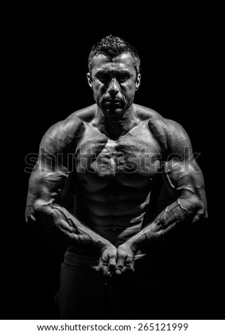 bodybuilder, posing on a black background - stock photo