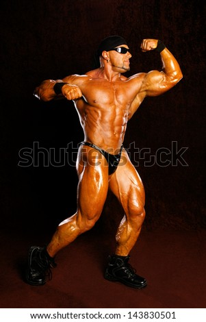 Bodybuilder posing on a dark background - stock photo