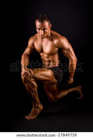 Bodybuilder posing on black background. - stock photo