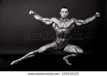 Bodybuilder posing on dark background - BW shot - stock photo