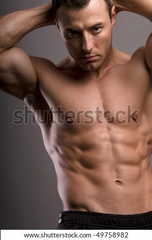 bodybuilder posing,on grey background. - stock photo